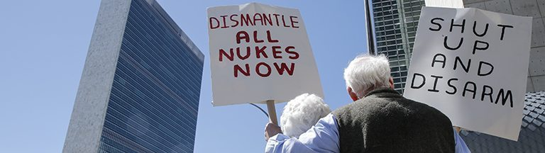NEW YORK, NY - APRIL 28: An old couple hold placards as they take part in a nuclear disarmament protest outside the United Nations (UN) headquarters in New York on April 28, 2015. (Photo by Bilgin S. Sasmaz/Anadolu Agency/Getty Images)